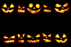 Halloween Pumpkins on black. Many Halloween Pumpkin glowing faces in a row isolated on black background Stock Images
