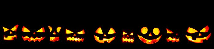 Halloween Pumpkins on black. Many Halloween Pumpkin glowing faces in a row isolated on black background Royalty Free Stock Photos