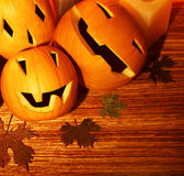 Halloween pumpkins border. Halloween pumpkins holiday border, autumn wooden background, traditional jack-o-lantern over wood with dry leaves, night party Stock Image