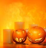 Halloween pumpkins border. Halloween pumpkins holiday border, with candles and smoke, traditional jack-o-lantern over warm yellow light, night party decoration Stock Photos