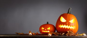 Halloween pumpkins and dry leaves Royalty Free Stock Photography