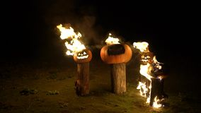 Halloween pumpkins in fire on tree log in darkness, field, mist, dusk. Scary funny angry big orange pumpkin exhales fire. Flame and smoke, breathes color steam stock video footage