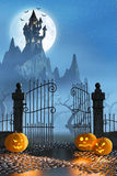Halloween pumpkins next to a gate of a spooky castle Stock Photos
