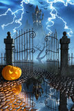Halloween pumpkins next to a gate of a spooky castle. Jack O`Lanterns guarding an open gate leading to a spooky castle high up in the mountains Royalty Free Stock Photography