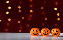 Halloween pumpkins with shiny lights. Halloween pumpkins on a shiny light dark red background Royalty Free Stock Image