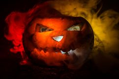 Halloween pumpkins smile and scrary eyes for party night. Close up view of scary Halloween pumpkin with eyes glowing inside at bla. Ck background. Selective Stock Photography
