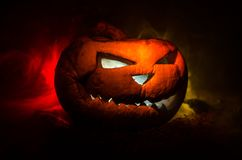 Halloween pumpkins smile and scrary eyes for party night. Close up view of scary Halloween pumpkin with eyes glowing inside at bla. Ck background. Selective Royalty Free Stock Photos