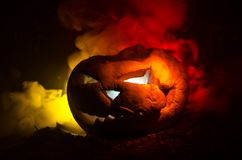 Halloween pumpkins smile and scrary eyes for party night. Close up view of scary Halloween pumpkin with eyes glowing inside at bla. Ck background. Selective Royalty Free Stock Photography