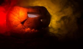 Halloween pumpkins smile and scrary eyes for party night. Close up view of scary Halloween pumpkin with eyes glowing inside at bla. Ck background. Selective Stock Photos