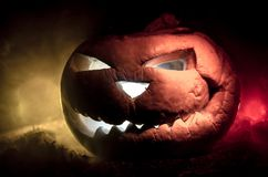 Halloween pumpkins smile and scrary eyes for party night. Close up view of scary Halloween pumpkin with eyes glowing inside at bla. Ck background. Selective Stock Image