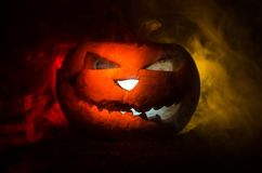 Halloween pumpkins smile and scrary eyes for party night. Close up view of scary Halloween pumpkin with eyes glowing inside at bla. Ck background. Selective Stock Photo