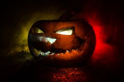 Halloween pumpkins smile and scrary eyes for party night. Close up view of scary Halloween pumpkin with eyes glowing inside at bla. Ck background. Selective Royalty Free Stock Photo