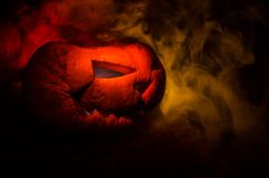 Halloween pumpkins smile and scrary eyes for party night. Close up view of scary Halloween pumpkin with eyes glowing inside at bla Royalty Free Stock Image