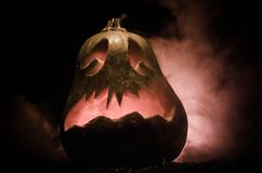 Halloween pumpkins smile and scrary eyes for party night. Close up view of scary Halloween pumpkin with eyes glowing inside at bla. Ck background. Selective Royalty Free Stock Images