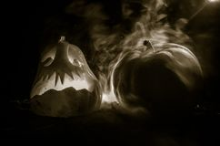 Halloween pumpkins smile and scrary eyes for party night. Close up view of scary Halloween pumpkin with eyes glowing inside at bla. Ck background. Selective Stock Images