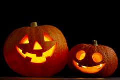 Halloween pumpkins. Two glowing Halloween pumpkins on black background Royalty Free Stock Photography