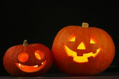 Halloween pumpkins. Two glowing Halloween pumpkins on black background Royalty Free Stock Image