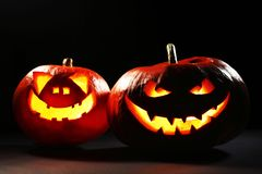 Halloween pumpkins. Two glowing Halloween pumpkins isolated on black background Stock Images