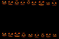 Halloween pumpkins wallpaper. On black Stock Image
