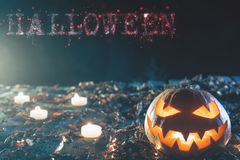 Halloween pumpkins at wood background with big text of HALLOWEEN Royalty Free Stock Photos