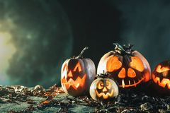 Halloween pumpkins at wood background. Carved scary faces of pumpkin. Royalty Free Stock Photos