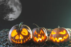 Halloween pumpkins at wood background. Carved scary faces of pumpkin. Stock Photography
