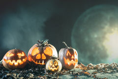 Halloween pumpkins at wood background. Carved scary faces of pumpkin. Stock Photos