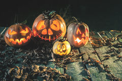 Halloween pumpkins at wood background. Carved scary faces of pumpkin. Royalty Free Stock Photography