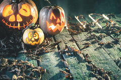 Halloween pumpkins at wood background. Carved scary faces of pumpkin. Stock Image