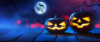 Halloween Pumpkins On Wood In A Spooky Forest At Night. With The Moon and Bats royalty free stock images