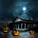 Halloween pumpkins in the yard of an old house at night Royalty Free Stock Images