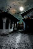 Halloween pumpkins in the yard of an old house at night Royalty Free Stock Photos