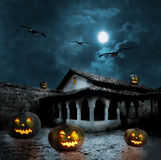 Halloween pumpkins in the yard of an old house at night Royalty Free Stock Photo