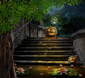 Halloween pumpkins in yard of of old stone staircase night Royalty Free Stock Photo