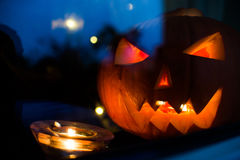 Halloween pupkin symbol behind the home window with light reflectons at night Royalty Free Stock Photos