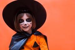 Halloween Ragazza vestita come strega su fondo arancio fotografia stock