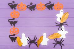 Halloween round frame with different paper silhouettes of pumpkins, cats, ghosts and spiders with autumn leaves Stock Photo