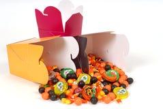 Halloween-Süßigkeit, die aus chinesischen Nahrungsmittelbehältern heraus fließt Stockfoto