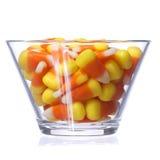 Halloween-Süßigkeitsmais in der Glasschüssel lokalisiert auf weißem Hintergrund Lizenzfreies Stockbild