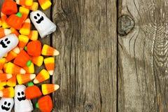Halloween-Süßigkeitsseitengrenze gegen rustikales Holz Lizenzfreies Stockbild