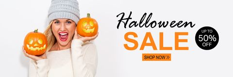 Halloween sale with woman holding pumpkins. Halloween sale with young woman holding pumpkins royalty free stock photo