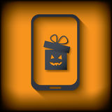 Halloween sales invitation in smartphone with gift Stock Photo