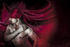 Halloween, sangue, vampiro spaventoso e maschio con il cappotto rosso enorme e blo Fotografie Stock Libere da Diritti