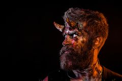 Halloween satan with beard, red blood, wounds on face profile. Man devil on black background. Holiday celebration, cosplay. Hell, death, evil, horror concept royalty free stock photography