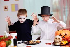 Halloween scare. Photo of twin eerie boys looking at camera with frightening look Royalty Free Stock Images