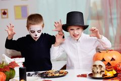 Halloween scare. Photo of twin eerie boys looking at camera with frightening look Royalty Free Stock Photo