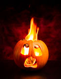 Halloween scared pumpkin with flames and red smoke. Evil face of Halloween pumpkin with flames and red smoke in the background Stock Image