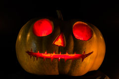 Halloween scary face pumpkin. On black background stock image