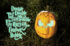 Halloween scary pumpkin and spell in the grass Royalty Free Stock Photo