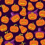 Halloween scary pumpkins vector seamless pattern. Dark purple background with orange funny faces in doodle style Stock Photography